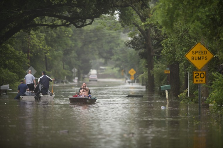 Charles Davidson and Jeremy Goodwin (back) use their boat to rescue Michelle Roper and her dog Charlee from her home off Kelly Ave. in Pensacola, Fla., on April 30, 2014. (REUTERS/Michael Spooneybarger)