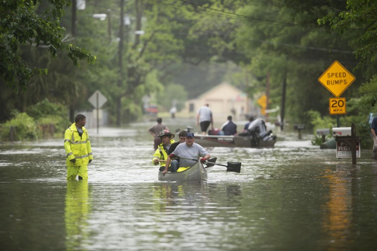 Rescue personal help residents out of flooding along Kelly Ave. in Pensacola, Fla., on April 30, 2014. (REUTERS/Michael Spooneybarger)