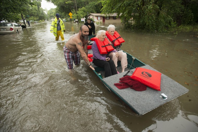 Charles Davidson helps his neighbors Millie Jones and Winnie Bunting during flooding in the Kelly Ave. Basin area of Pensacola, Fla., on April 30, 2014. (REUTERS/Michael Spooneybarger)