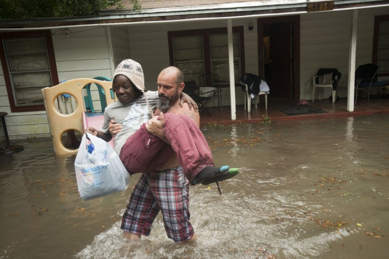 Charles Davidson helps his neighbor Santonio Coleman, 11, from his flooded home in the Kelly Ave. Basin area of Pensacola, Fla., on April 30, 2014. (REUTERS/Michael Spooneybarger)