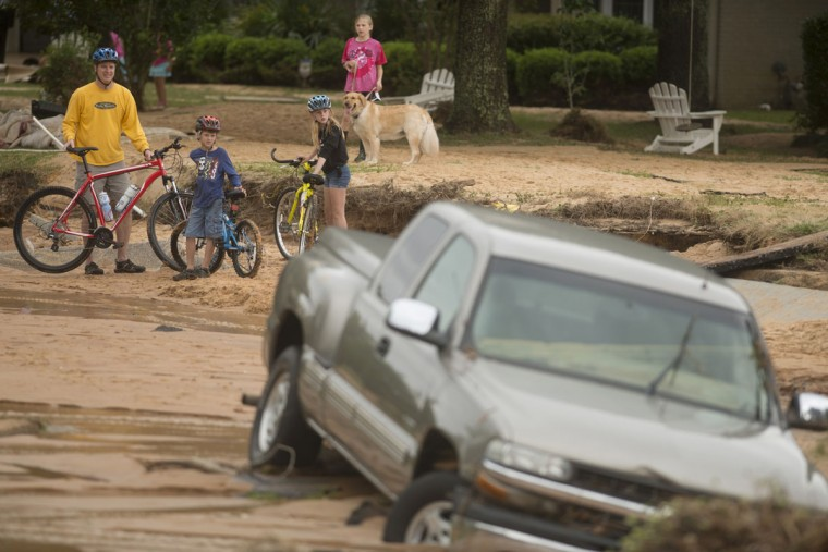 Residents survey flood damage to the Cordova Park neighborhood in Pensacola, Fla., on April 30, 2014. (REUTERS/Michael Spooneybarger)
