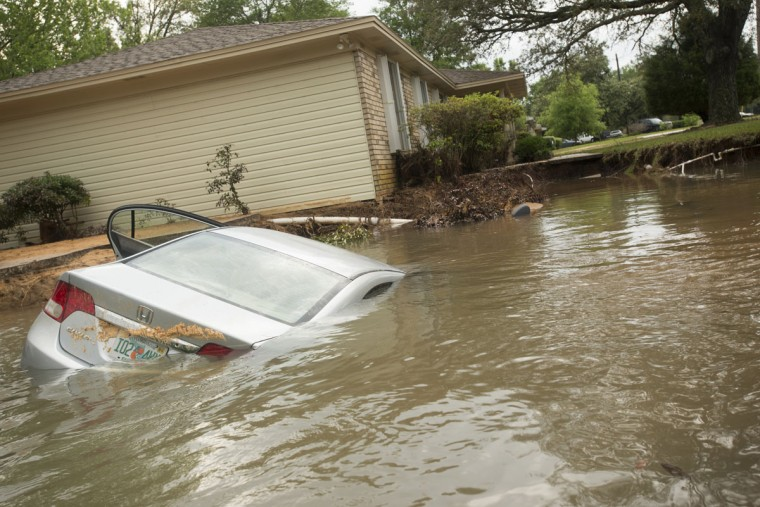A submerged car sits in the driveway in the Cordova Park neighborhood in Pensacola, Fla., on April 30, 2014. (REUTERS/Michael Spooneybarger)