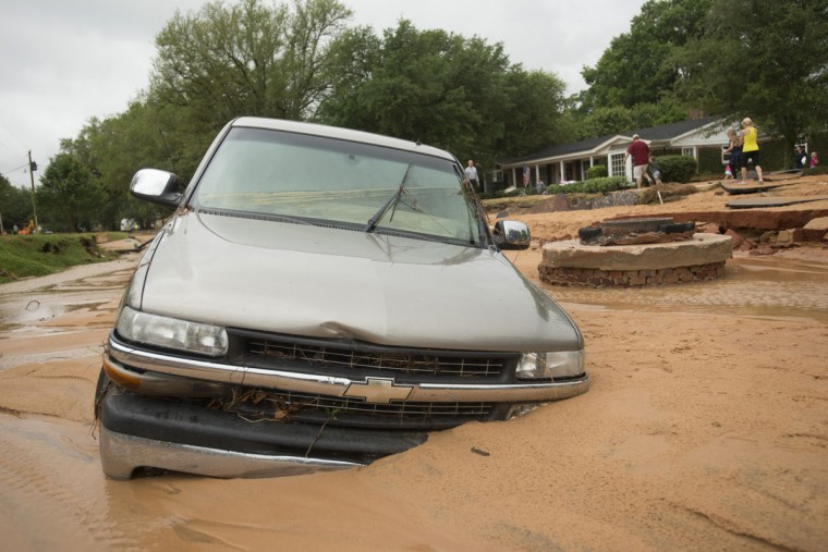 A vehicle is left partially submerged after flash flooding in the Cordova Park neighborhood in Pensacola, Fla., on April 30, 2014. (REUTERS/Michael Spooneybarger)