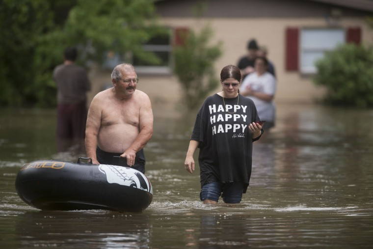 Bruce Woerner and his daughter Kelly Woerner walk to dry land in their Kelly Ave. Basin neighborhood after heavy rain in Pensacola, Fla., on April 30, 2014. (REUTERS/Michael Spooneybarger)