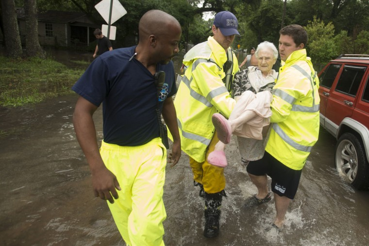 Winnie Bunting is carried to an ambulance after being rescued from her flooded home in the Kelly Ave Basin area of Pensacola, Fla., on April 30, 2014. (REUTERS/Michael Spooneybarger)