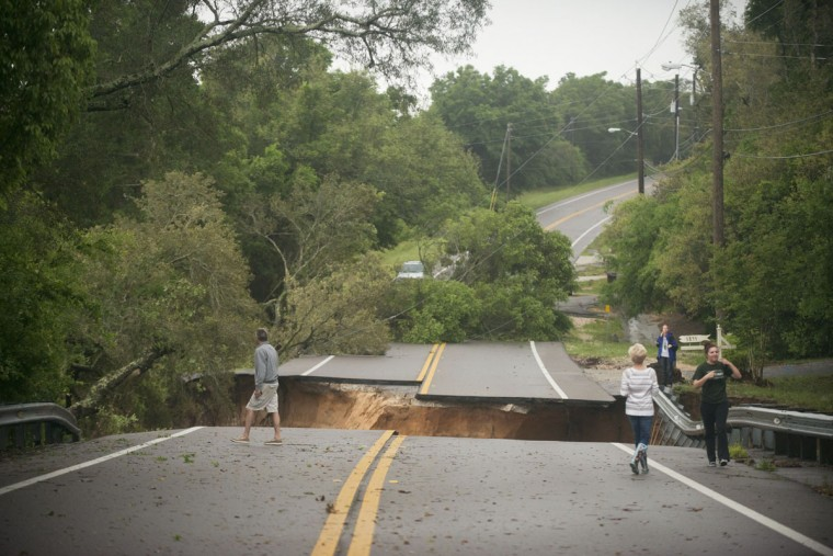 Residents look at the washed out area of Scenic Hwy 90 after heavy rains and flooding damage in Pensacola, Fla., on April 30, 2014. (REUTERS/Michael Spooneybarger)