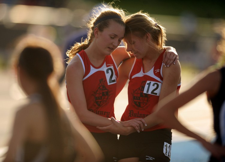 Dulaney teammates Isabel Griffith, left, and Kristin Meek hold each other up as they catch their breath following an exhausting run in the 4A girls 3200 meter run during the 2014 track and field state championships at Morgan State University. (Brian Krista/BSMG)