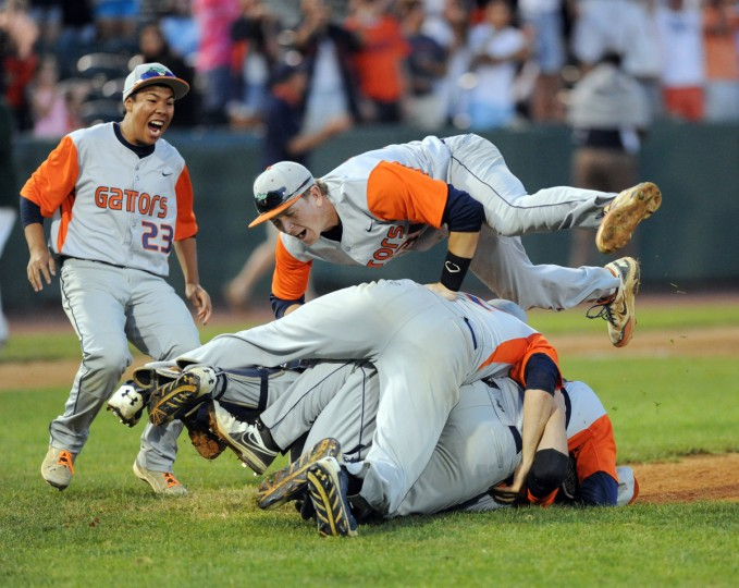 Reservoir's Jon Mierzwa dives on top of the pile to celebrate with his teammates and winning pitcher Cody Morris after the final out in the Class 3A State Championship win over North Harford at Ripken Stadium in Aberdeen. (Matt Button/BSMG)
