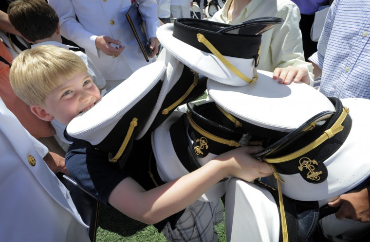 Keegan Clifford,8, of Severna Park collected eight midshipman hats after the hat toss. The newly commissioned Navy and Marine Corps officers toss their hats into the air upon the conclusion of the graduation ceremonies. Lloyd Fox/Baltimore Sun