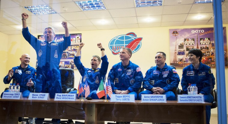 Expedition 40 Flight Engineer Alexander Gerst of the European Space Agency (ESA), Soyuz Commander Maxim Suraev of the Russian Federal Space Agency (Roscosmos) and Flight Engineer Reid Wiseman of NASA, celebrate during a press conference at the Cosmonaut Hotel May 27, 2014 in Baikonur, Kazakhstan. Suraev, Roscosmos, Flight Engineer Alexander Gerst of the European Space Agency (ESA) and Flight Engineer Reid Wiseman of NASA will launch aboard a Soyuz spacecraft to the International Space Station on May 29. Photo Joel Kowsky/NASA via Getty Images)