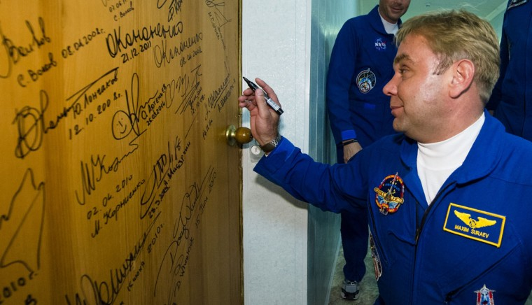 Expedition 40 Soyuz Commander Maxim Suraev of the Russian Federal Space Agency (Roscosmos) performs the traditional door signing at the Cosmonaut Hotel prior to departing the hotel for launch May 28, 2014 in Baikonur, Kazakhstan. Suraev, Gerst and Wiseman will launch aboard a Soyuz spacecraft to the International Space Station on May 29. (Photo Joel Kowsky/NASA via Getty Images)