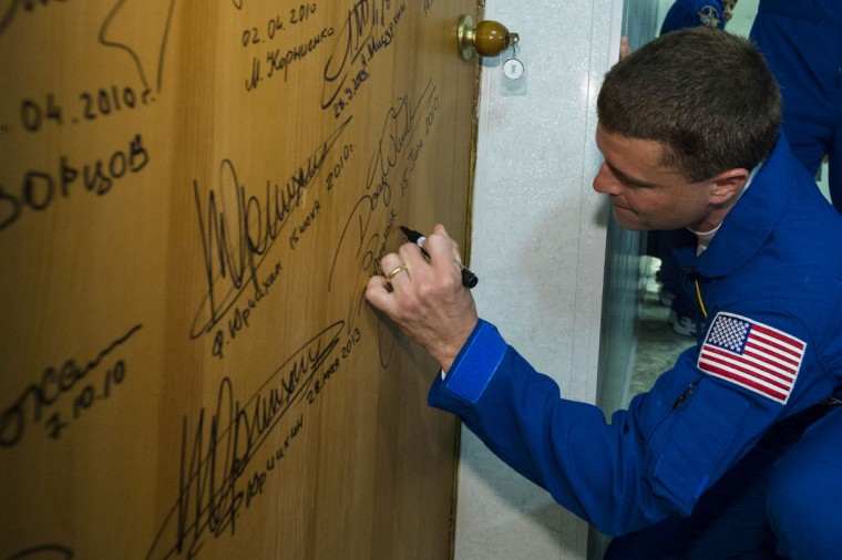 Flight Engineer Reid Wiseman of NASA, performs the traditional door signing at the Cosmonaut Hotel prior to departing the hotel for launch May 28, 2014 in Baikonur, Kazakhstan. Suraev, Gerst and Wiseman will launch aboard a Soyuz spacecraft to the International Space Station on May 29. (Photo Joel Kowsky/NASA via Getty Images)