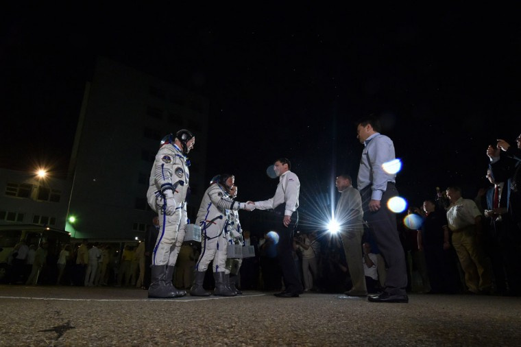 European Space Agency's German astronaut Alexander Gerst (L), Russian cosmonaut Maxim Suraev (2ndL) and US NASA astronaut Gregory Wiseman shake hands with head of Russia's Space agengy Oleg Ostapenko (2ndR) after their space suits were tested at the Russian-leased Baikonur cosmodrome, prior to blasting off to the International Space Station (ISS) late on May 28, 2014 . The launch of the Soyuz TMA-13M with the international crew aboard is scheduled early on May 29 local time. (Kirill Kudryavtsev/AFP/Getty Images)