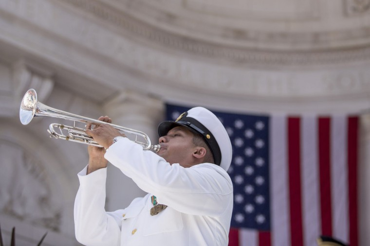 """A member of the U.S. Navy plays """"Taps"""" after U.S. President Barack Obama delivered remarks during a Memorial Day event at Arlington National Cemetery, May 26, 2014 in Arlington, Virginia. Obama returned to Washington the morning of May 26, after a surprise visit to Afghanistan to visit U.S. troops at Bagram Air Field. (Pool photo by Drew Angerer/Getty Images)"""
