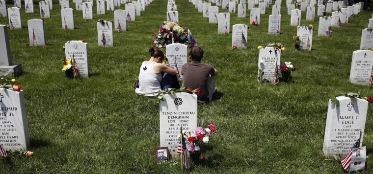 People visit graves in Section 60, where many casualties of the U.S. wars in Iraq and Afghanistan are buried, on Memorial Day at Arlington National Cemetery in Arlington, Virginia May 26, 2014. President Obama marked Memorial Day and the 150th anniversary of the cemetery Monday by laying a wreath to honor the soldiers buried there since the Civil War. REUTERS/Jonathan Ernst