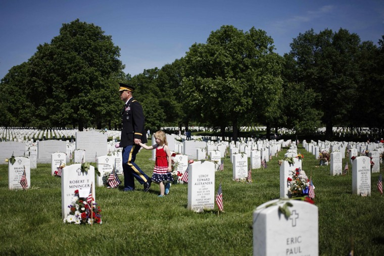 Visitors walk between graves in Section 60, where many casualties of the U.S. wars in Iraq and Afghanistan are buried, on Memorial Day at Arlington National Cemetery in Arlington, Virginia May 26, 2014. President Obama marked Memorial Day and the 150th anniversary of the cemetery Monday by laying a wreath to honor the soldiers buried there since the Civil War. REUTERS/Jonathan Ernst