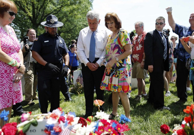 U.S. Defense Secretary Chuck Hagel (center L) stands with Karen Meredith (center R) at her son U.S. Army Lieutenant Ken Ballard's grave in Section 60, where many casualties of the U.S. wars in Iraq and Afghanistan are buried, on Memorial Day at Arlington National Cemetery in Arlington, Virginia May 26, 2014. This year Meredith is marking the tenth anniversary of Ballard's death, which occured in Najaf, Iraq, on Memorial Day in 2004. REUTERS/Jonathan Ernst
