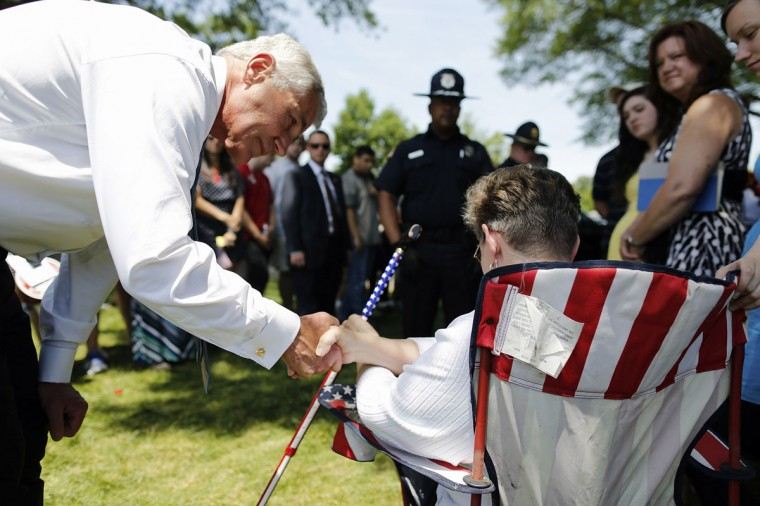 U.S. Defense Secretary Chuck Hagel (L) greets family members amongst the graves in Section 60, where many casualties of the U.S. wars in Iraq and Afghanistan are buried, on Memorial Day at Arlington National Cemetery in Arlington, Virginia May 26, 2014. REUTERS/Jonathan Ernst