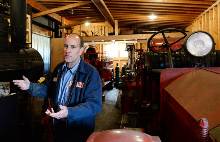 Scott Shearer, of Highland, talks about some of his antique firetrucks in one of his garages on his farm. (Jon Sham/BSMG)