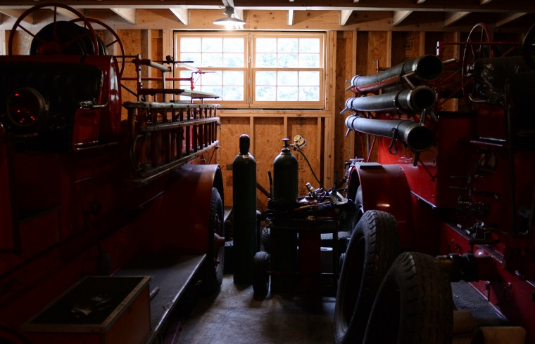 Two antique fire trucks sit in the back of one of Scott Shearer's garages on his Highland farm with tools, parts and other eqiupment all around. (Jon Sham/BSMG)