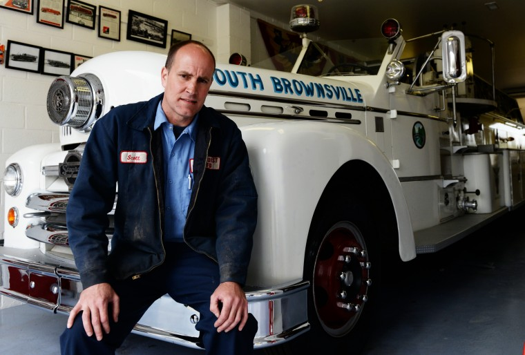 Scott Shearer poses for a photo while sitting on one of his antique firetrucks on his farm in Highland. (Jon Sham/BSMG)