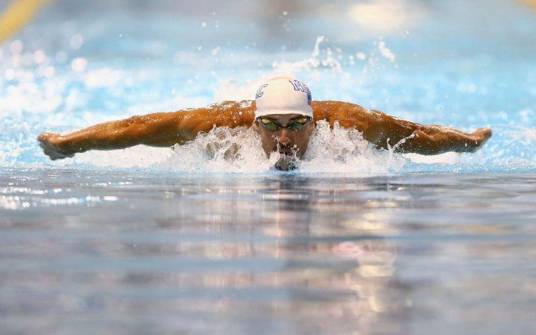 Michael Phelps competes in the men's 100m butterfly preliminaries during day 1 of the Arena Grand Prix at Charlotte at Mecklenburg County Aquatic Center on May 16, 2014 in Charlotte, North Carolina. (Streeter Lecka/Getty Images)