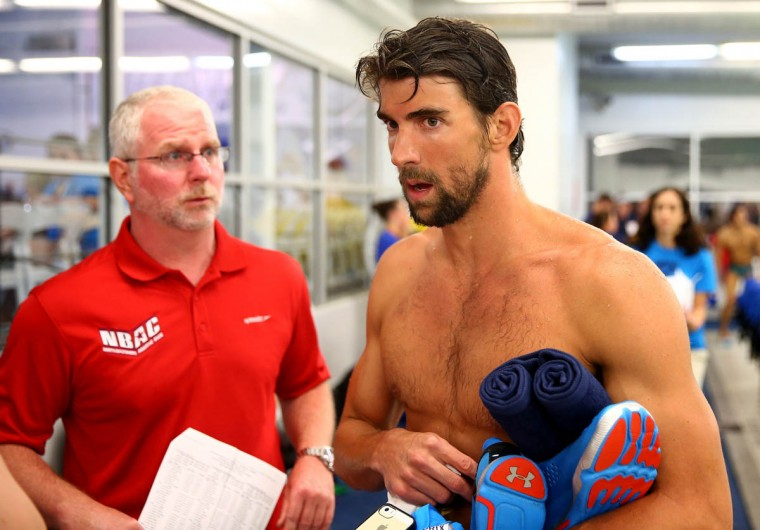 Coach Bob Bowman, left, and Michael Phelps talk after his swim in the men's 100m butterfly final during day 1 of the Arena Grand Prix at Charlotte at Mecklenburg County Aquatic Center on May 16, 2014 in Charlotte, North Carolina. ((Streeter Lecka/Getty Images)