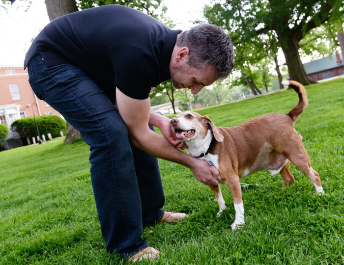 "Essam Shomali pets his dog Little Joe in a park by their house in the Rodgers Forge neighborhood of Towson on Thursday, May 22, 2014. Little Joe has been diagnosed with terminal cancer, and his owners, Essam and Kathryne Shomali, have compiled a ""bucket list"" for him. (Jon Sham/BSMG)"