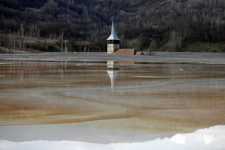 The old church of Geamana village is seen partially submerged by polluted water tainted with cyanide and other chemicals near Rosia Montana, central Romania, March 24, 2014. Romania's lower house rejected a bill on June 3 that would have enabled Canada's Gabriel Resources to set up Europe's biggest open-cast gold mine in the small Carpathian town of Rosia Montana, putting the project on hold indefinitely. The bill, which was initially approved by the leftist government of Prime Minister Victor Ponta, drew thousands of anti-mine protesters into the streets across the European Union state last year, prompting the senate to strike it down. The sight of a nearby tailings pond that is the product of a decades-old industrial project, has been used by protesters to highlight fears about the potential fallout of the gold mine. State-owned copper miner Cupru Min started that pond in the 1970s under the communist regime when it poured polluted water tainted with cyanide and other chemicals that result from copper extraction over the village of Geamana, not far from Rosia Montana in Alba county. (Bogdan Cristel/Reuters photo)