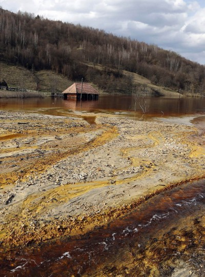 A polluted lake, tainted with cyanide and other chemicals, is seen covering Geamana village near Rosia Montana, central Romania, March 24, 2014. Romania's lower house rejected a bill on June 3 that would have enabled Canada's Gabriel Resources to set up Europe's biggest open-cast gold mine in the small Carpathian town of Rosia Montana, putting the project on hold indefinitely. The bill, which was initially approved by the leftist government of Prime Minister Victor Ponta, drew thousands of anti-mine protesters into the streets across the European Union state last year, prompting the senate to strike it down. The sight of a nearby tailings pond that is the product of a decades-old industrial project, has been used by protesters to highlight fears about the potential fallout of the gold mine. State-owned copper miner Cupru Min started that pond in the 1970s under the communist regime when it poured polluted water tainted with cyanide and other chemicals that result from copper extraction over the village of Geamana, not far from Rosia Montana in Alba county. (Bogdan Cristel/Reuters photo)