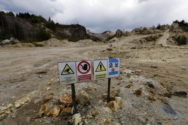 Warning signs are seen next to an old quarry near Rosia Montana, central Romania, March 24, 2014. Romania's lower house rejected a bill on June 3 that would have enabled Canada's Gabriel Resources to set up Europe's biggest open-cast gold mine in the small Carpathian town of Rosia Montana, putting the project on hold indefinitely. The bill, which was initially approved by the leftist government of Prime Minister Victor Ponta, drew thousands of anti-mine protesters into the streets across the European Union state last year, prompting the senate to strike it down. (Bogdan Cristel/Reuters photo)