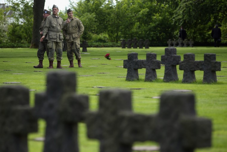D-Day re-enactment enthusiasts dressed as World War II American soldiers walk among gravestones at the German Cemetery where approximately 21,000 German World War II soldiers are buried on June 5, 2014 at La Cambe, France. (Sean Gallup/Getty Images)