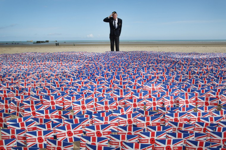 WW2 veteran Fred Holborn, from the Fleet Air Arm, salutes as he looks at British Legion Union flags carrying thank you messages planted in the sand on Gold beach on June 5, 2014 near Asnelles, France. 20,000 paper flags are being planted. Each one carries a personal message of Remembrance submitted by Royal British Legion supporters. (Peter Macdiarmid/Getty Images)