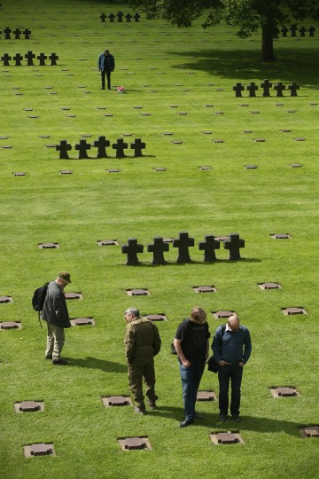 Visitors walk among gravestones at the German Cemetery where approximately 21,000 German World War II soldiers are buried on June 5, 2014 at La Cambe, France. (Sean Gallup/Getty Images)