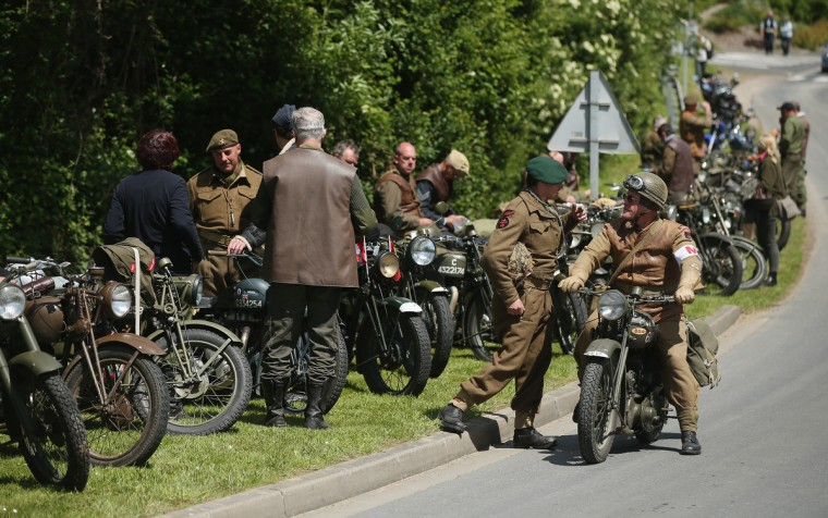 D-Day re-enactment enthusiasts dressed in World War II Allied military informs stand with their period-era motorcycles on June 5, 2014 at Benouville, France. (Sean Gallup/Getty Images)