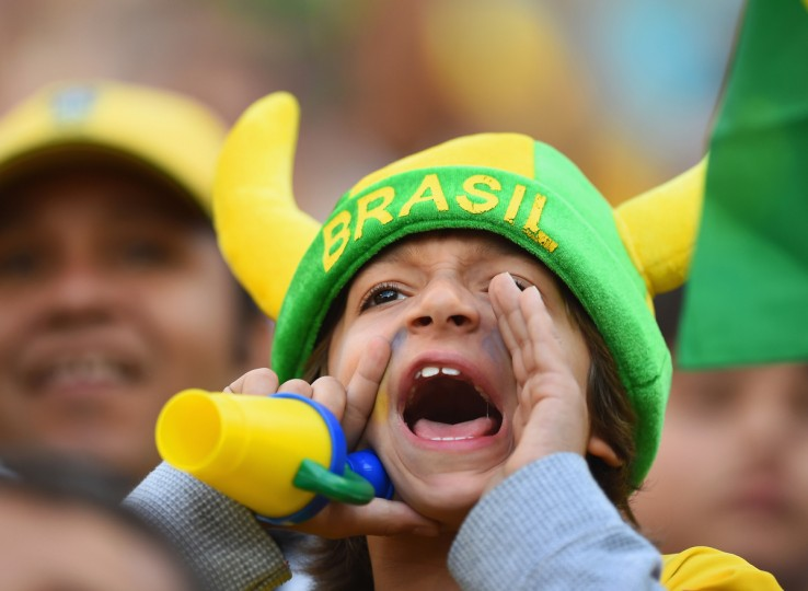 A young fan cheers before the 2014 FIFA World Cup Brazil Group A match between Brazil and Croatia at Arena de Sao Paulo on June 12, 2014 in Sao Paulo, Brazil. (Christopher Lee/Getty Images)