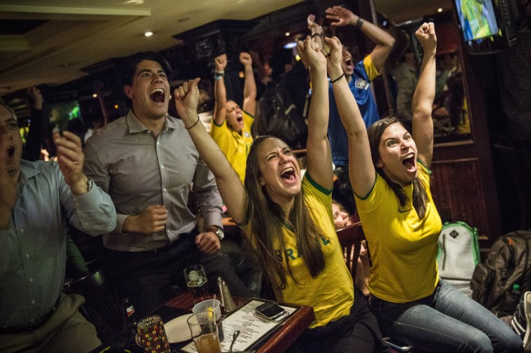 Brazilian soccer fans react after Brazil's first goal in the Brazil vs. Crotia World Cup game at Legends Bar on June 12, 2014 in New York City. Brazil vs Crotia is the first game of the World Cup, which will take place throughout Brazil until Sunday, July 13. (Andrew Burton/Getty Images)