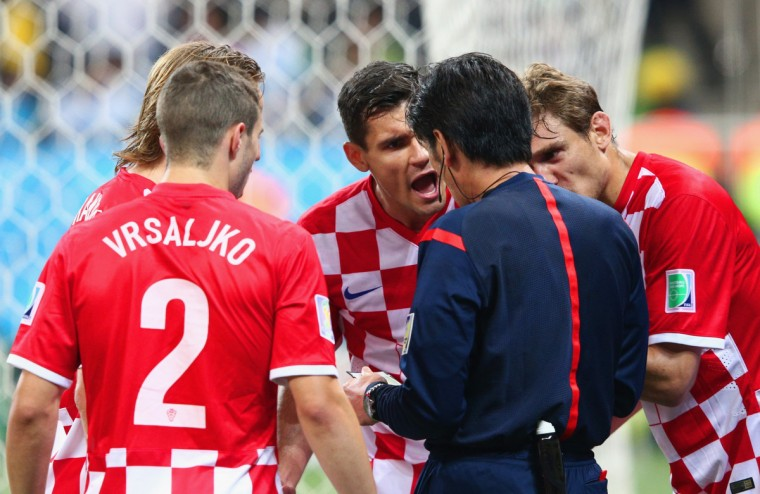 Referee Yuichi Nishimura speaks with Sime Vrsaljko (L) and Dejan Lovren of Croatia (C) after giving Lovren a yellow card and awarding a penalty kick during the 2014 FIFA World Cup Brazil Group A match between Brazil and Croatia at Arena de Sao Paulo on June 12, 2014 in Sao Paulo, Brazil. (Adam Pretty/Getty Images)