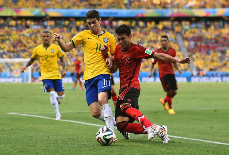 Oscar of Brazil and Hector Moreno of Mexico battle for the ball during the 2014 FIFA World Cup Brazil Group A match between Brazil and Mexico at Castelao on June 17, 2014 in Fortaleza, Brazil. (Laurence Griffiths/Getty Images)