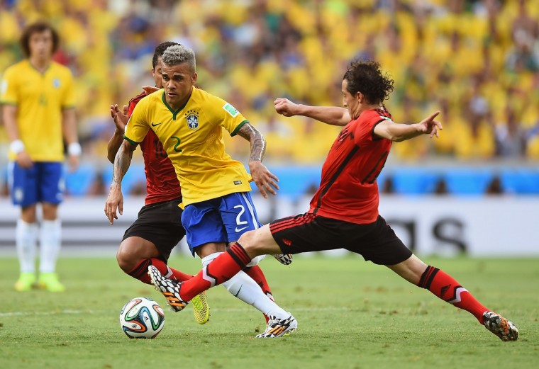 Dani Alves of Brazil is challenged by Giovani dos Santos (L) and Andres Guardado of Mexico during the 2014 FIFA World Cup Brazil Group A match between Brazil and Mexico at Castelao on June 17, 2014 in Fortaleza, Brazil. (Laurence Griffiths/Getty Images)