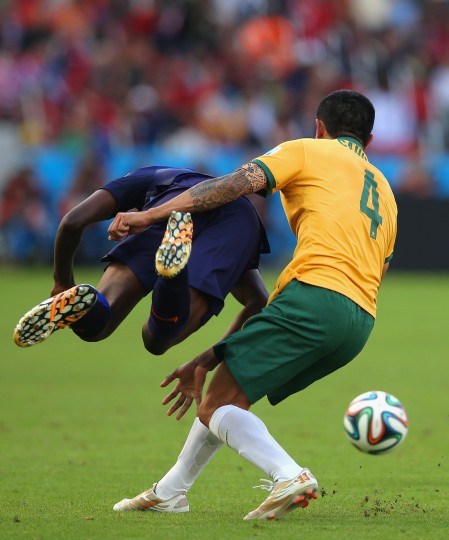 Bruno Martins Indi of the Netherlands falls to the field after a challenge by Australia during the 2014 FIFA World Cup Brazil Group B match between Australia and Netherlands at Estadio Beira-Rio on June 18, 2014 in Porto Alegre, Brazil. (Photo by Dean Mouhtaropoulos/Getty Images)