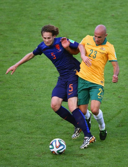 Daley Blind of the Netherlands and Mark Bresciano of Australia battle for the ball during the 2014 FIFA World Cup Brazil Group B match between Australia and Netherlands at Estadio Beira-Rio on June 18, 2014 in Porto Alegre, Brazil. (Photo by Paul Gilham/Getty Images)