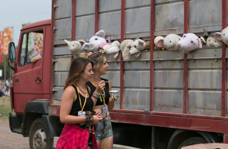 Festival goers react to a sculpture by Banksy, entitled 'The Sirens of the Lambs', depicting a truck full of shrieking cuddly animals being driven to slaughter, driving around the Glastonbury Festival, at Worthy Farm in Pilton on the second day of the 2014 Glastonbury Festival on June 26, 2014 in Glastonbury, England. (Matt Cardy/Getty Images)