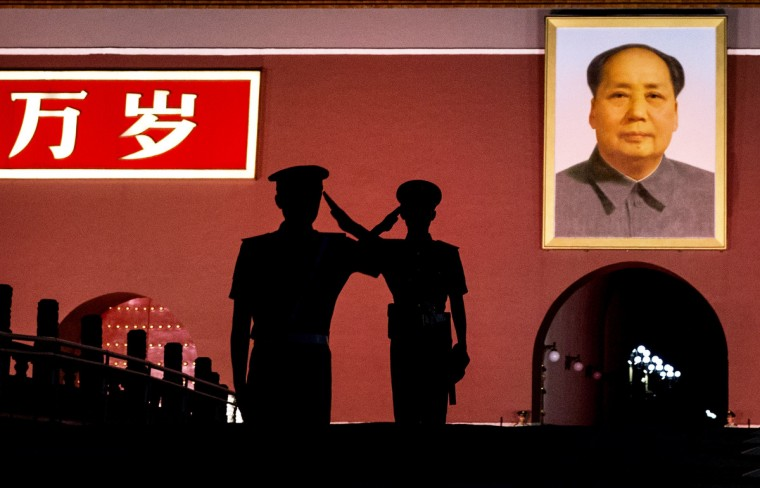 Chinese Paramilitary police officers salut each other as they stand guard below a portrait of the late leader Mao Zedong in Tiananmen Square in Beijing, China. Twenty-five years ago on June 4, 1989 Chinese troops cracked down on pro-democracy protesters and in the clashes that followed scores were killed and injured. (Kevin Frayer/Getty Images)