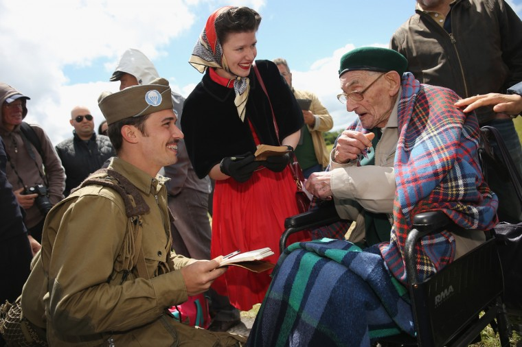 Historical re-enactment enthusiasts and siblings Joshua and Faith Phillips from San Antonio, Texas, chat with Irish World War II veteran Robert McLaughlin, 90, at Carentan, France. McLaughlin was a commando in the Ulster Rifles of the British Army, participated in the capture of Pegasus Bridge during the D-Day invasion in 1944 and is visiting Normandy for the first time since the war. Friday the 6th of June is the 70th anniversary of the D-Day landings that saw 156,000 troops from the Allied countries, including the United Kingdom and the United States, join forces to launch an audacious attack on the beaches of Normandy, these assaults are credited with the eventual defeat of Nazi Germany. A series of events commemorating the 70th anniversary are planned for the week with many heads of state travelling to the famous beaches to pay their respects to those who lost their lives. (Sean Gallup/Getty Images)