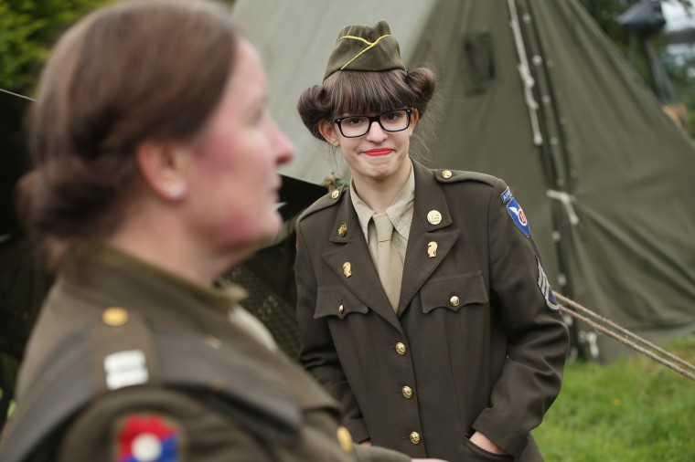 Female historical D-Day re-enactment enthusiasts dressed as American service women attend a re-enactment camp on June 4, 2014 in Sainte Mere Eglise, France. (Sean Gallup/Getty Images)