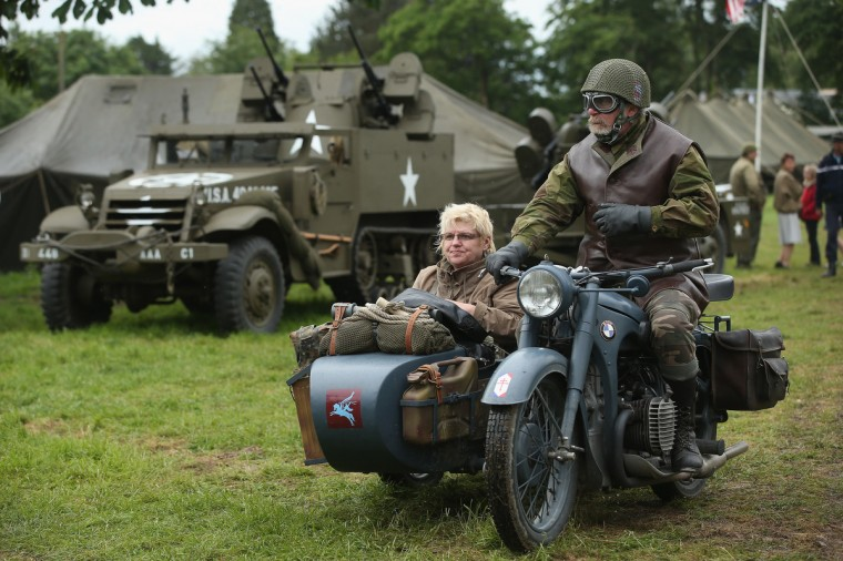 D-Day re-enactment enthusiasts dressed as Allied soldiers ride a World War II-era motorcycle and sidecar through a re-enactment camp on June 4, 2014 in Sainte Mere Eglise, France. (Sean Gallup/Getty Images)