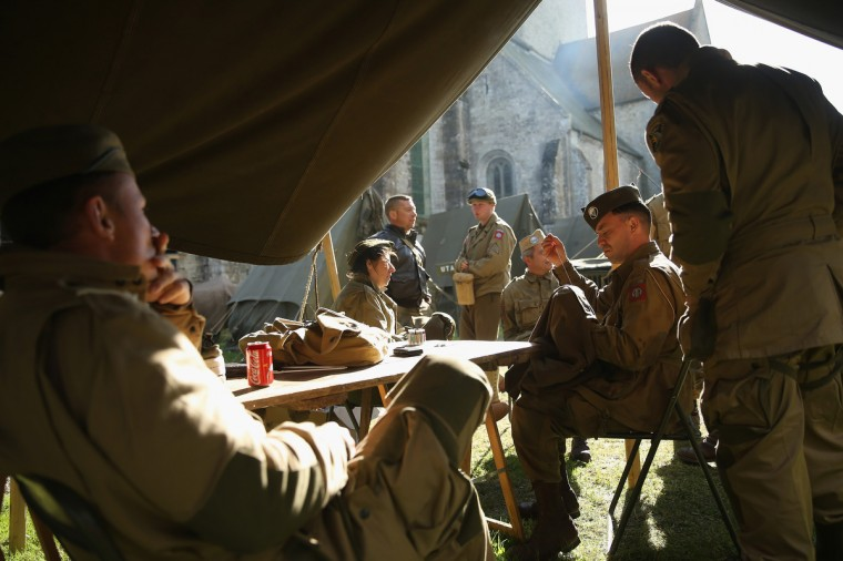 D-Day re-enactment enthusiasts dressed as World War II American soldiers relax at their camp outside the church on June 4, 2014 near Utah Beach in Sainte Marie du Mont, France. (Sean Gallup/Getty Images)
