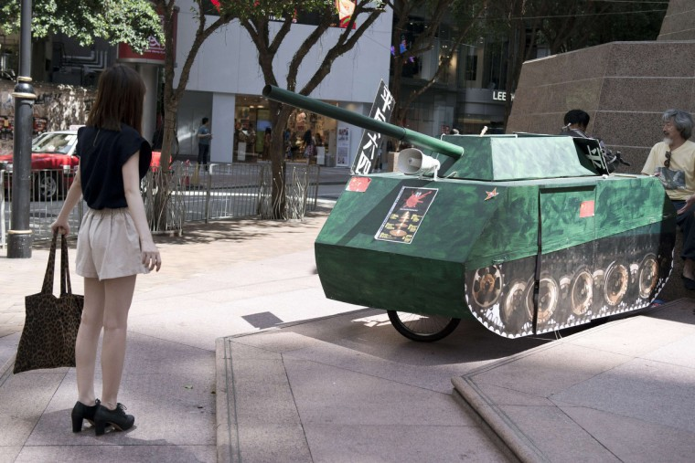 "A young woman reenacts the famous ""Tank Man"" scene from the 1989 Tiananmen Square military crackdown on pro-democracy protesters om Beijing, in front of a replica of a Chinese tank in Hong Kong. Up to 200,000 people were set to take part in a candlelight vigil in Hong Kong on June 4 to commemorate the 25th anniversary of the bloody Tiananmen Square crackdown, as China seeks to wipe the incident from memory. (Alex Ogle/Getty Images)"