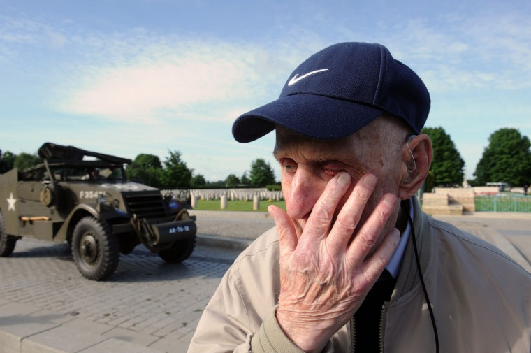 British World War II veteran Harry Humphreys, 92, from the 4th Royal Dragon Guard, reacts after his visit at Bayeux's war cemetery, while an old allied military vehicle passes by, in northern France, on June 5, 2014, a day before the start of the D-Day commemorations. (Jean-Francois Monier/Getty Images)